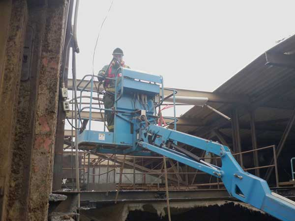 Using a lift, worker with torch cuts steel beams.